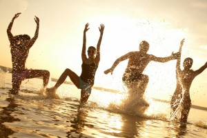 A group of people in shallow water jumping for joy
