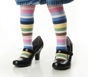 A child's legs wearing horizontal striped, multi colored tights and adult women's black pumps