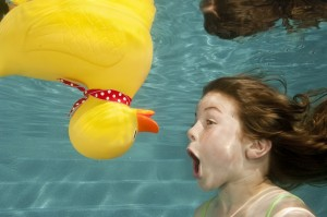 Under water photo of an upside down rubber duck floating in a pool will a shocked brown haired girl under water looking at the duck.